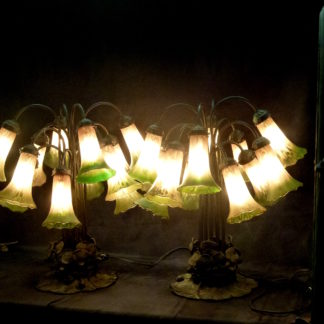 788. Pair of Tiffany type Lily Pad and Lotus Flower table lamps.Each lamp has twelve shades all in good condition. The base is metal with a green patina. No name of the maker I would put the age at ca.1940. H. 22in (56cm). Lamps are very heavy. Unusual to see twelve shades per lamp $1450.00